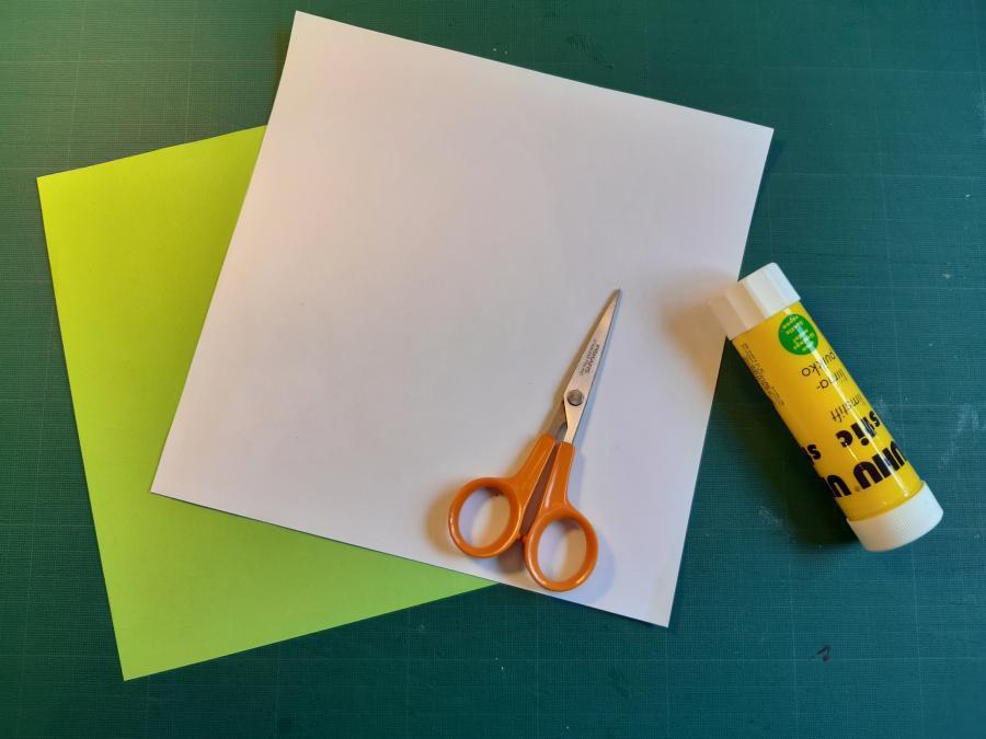 To stykker papir, et hvidt og et farvet, en saks og noget lim.