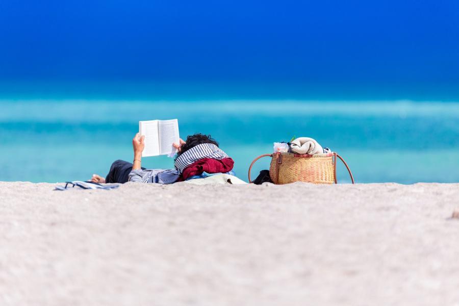 Foto af en kvinde, der læser på en strand