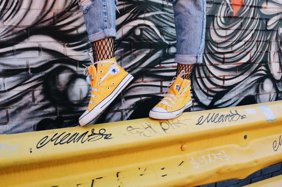 Et par fødder i gule gummisko