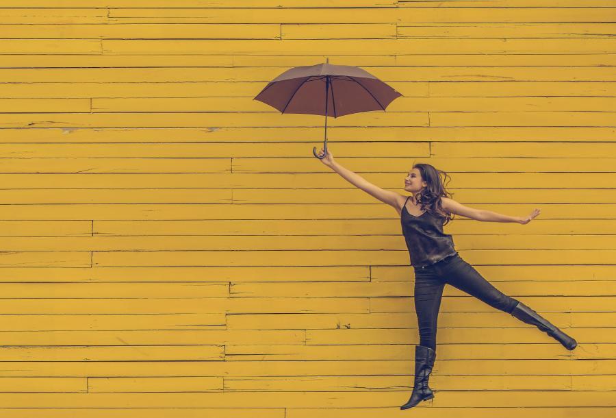 Glad ung pige med paraply. Foto: Edu Lauton, Unsplash
