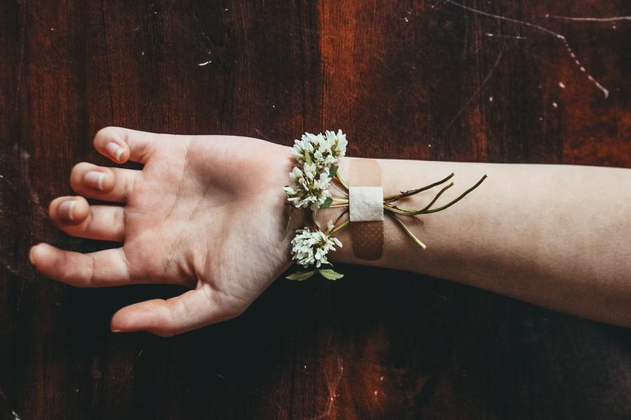 En arm med plaster på indersiden af håndledet, Foto fra Unsplash