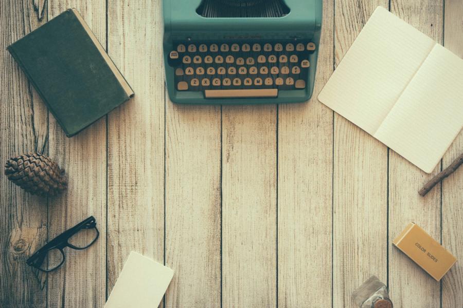 Skrivebord set fra oven med skrivemaskine, briller ol. Foto fra Unsplash
