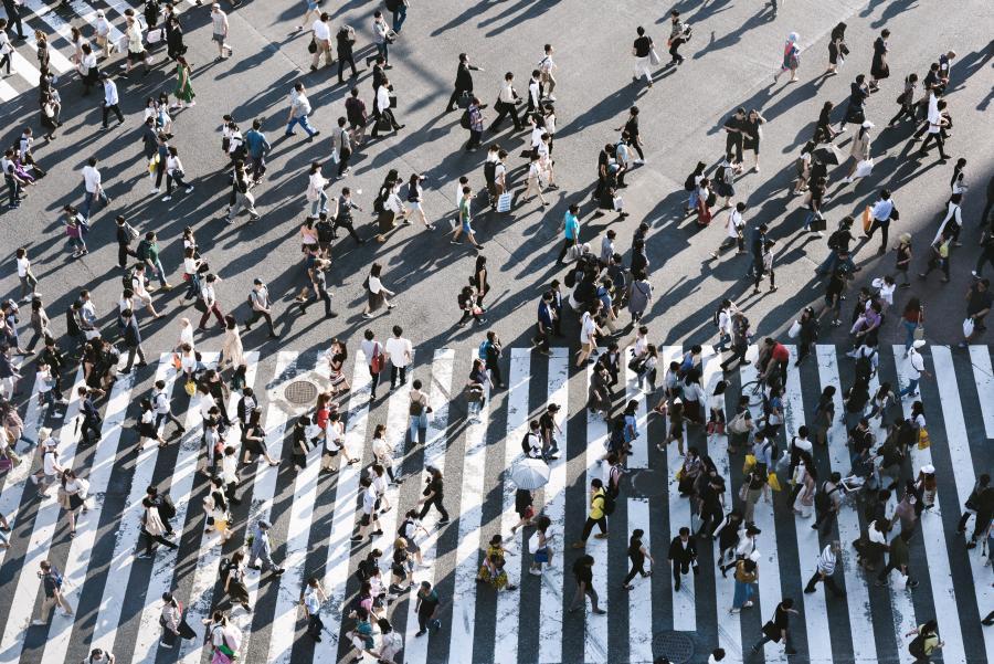 En masse mennesker set fra oven, gå rundt på gaden. Foto fra Unsplash
