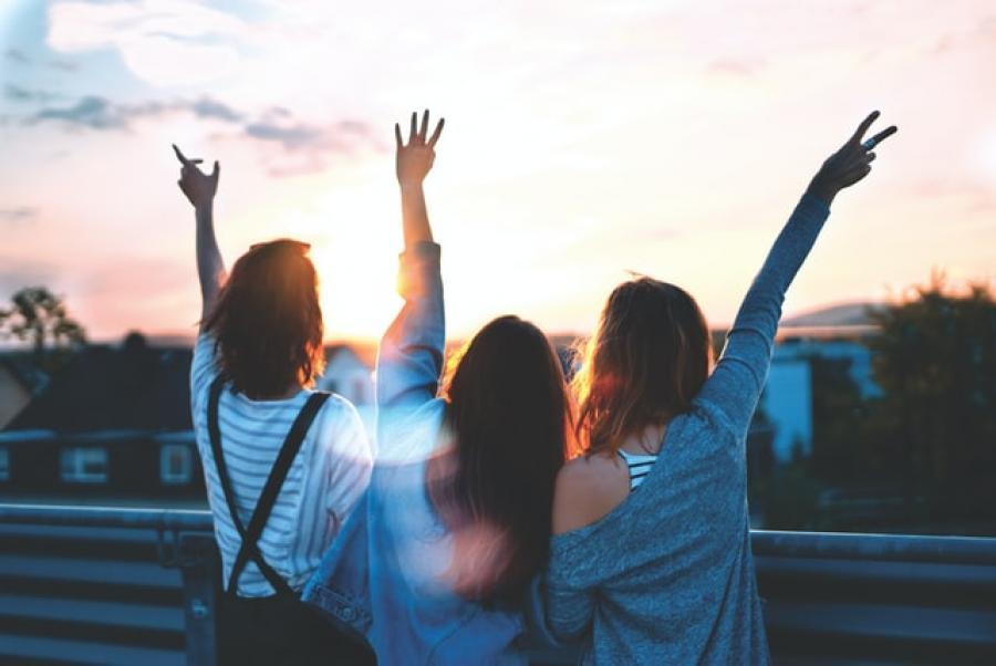 Tre unge mennesker ses i solnedgangen med armene i vejret