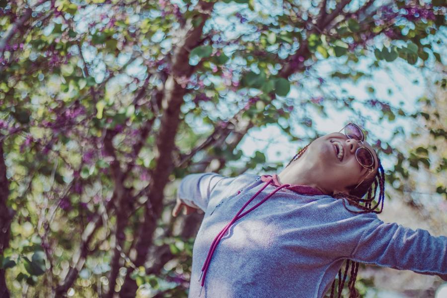 Foto af kvinde ved blomstrende kirsebærtræer